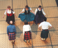 A set of three costumed couples bowing and curtsying as part of a performance